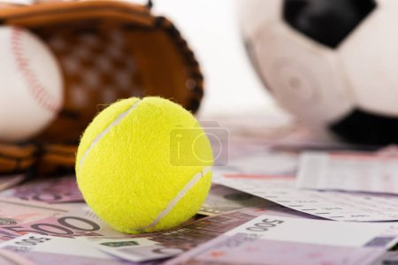 Mise au point sélective du ballon de tennis près du ballon de football, du gant de baseball et du ballon sur les billets en dollars et en euros isolés sur le blanc, concept de paris sportifs