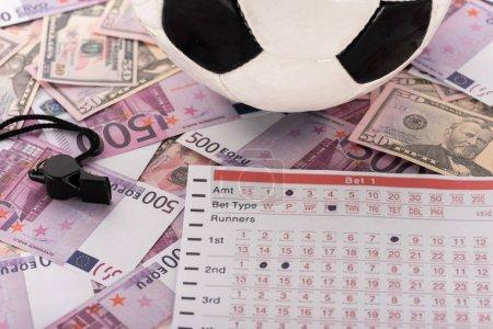 Photo pour Balle de football, sifflet et liste de paris sur les billets en euros et en dollars, concept de paris sportifs - image libre de droit