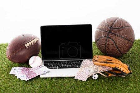 Photo pour Ordinateur portable près des balles de sport, gant de baseball, billets en euros et en dollars sur herbe verte isolé sur blanc, concept de paris sportifs - image libre de droit