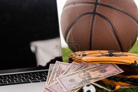 Photo pour Vue rapprochée des billets en dollars dans un gant de baseball près d'un ballon de football jouet, d'un ordinateur portable et d'une balle de basket isolés sur du blanc, concept de paris sportifs - image libre de droit