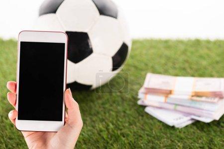 Photo pour Vue partielle de la main féminine avec smartphone près de paquets d'argent et ballon de football sur herbe verte isolé sur blanc, concept de paris sportifs - image libre de droit