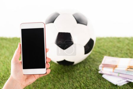 Photo pour Vue recadrée de la main féminine avec smartphone près de paquets d'argent et ballon de football sur herbe verte isolé sur blanc, concept de paris sportifs - image libre de droit
