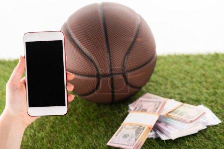 Photo pour Vue recadrée de la main féminine avec smartphone près de paquets d'argent et ballon de basket sur herbe verte isolé sur blanc, concept de paris sportifs - image libre de droit