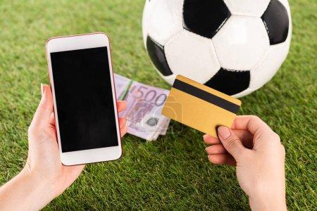Photo pour Vue recadrée des mains féminines avec smartphone et carte de crédit près du ballon de football et billets en euros sur herbe verte, concept de paris sportifs - image libre de droit