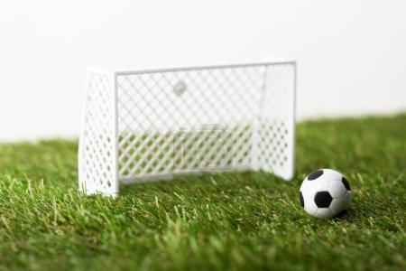 Foto de Toy football gates and ball on green grass isolated on white, sports betting concept - Imagen libre de derechos