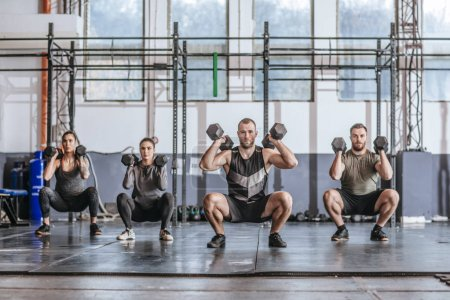 Photo for Group of sportsmen and sportswomen doing squats with weights at gym. - Royalty Free Image