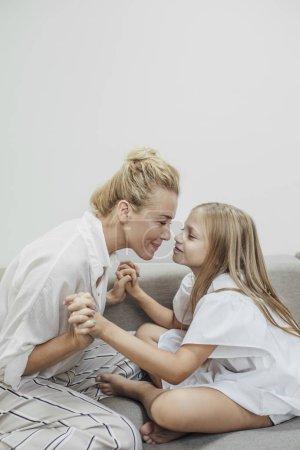 Portret matki i córki, przytulanie w domu.