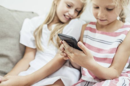 Two cute Caucasian girls sisters sitting at home and looking at cell phone.
