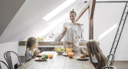 Two cute Caucasian girls sisters enjoying breakfast at home with their beautiful mother.