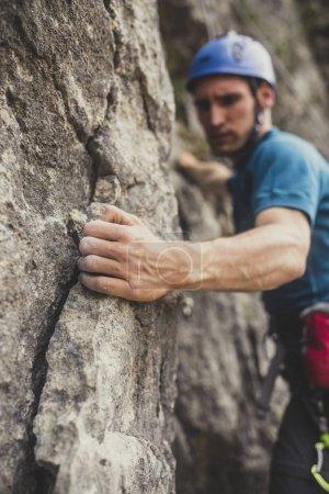 A man climbing an outdoor natural rock.