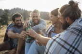 Group of young people drinking beer in nature and looking happy.