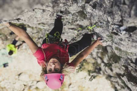 Photo for Female alpinist climbing a rock. - Royalty Free Image