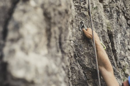 Unrecognisable man climbing a natural rock.