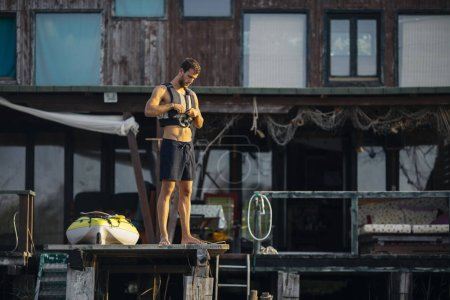 Handsome Caucasian sportsman kayaker standing on wooden deck by the river and putting life jacket on.