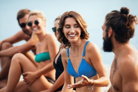 Group of smiling people in swimwear enjoying summertime together.