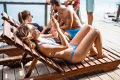 Beautiful woman in wearing bikini lying on deck on river and enjoying summertime.