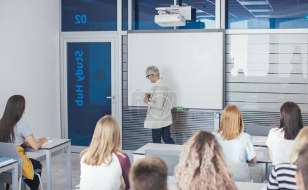 Pretty middle-aged woman teacher teaching a lesson at high school.