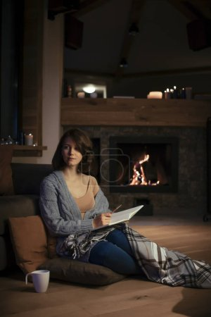 Photo pour Belle femme assise près de la cheminée dans un pull confortable et écrivant dans un cahier . - image libre de droit