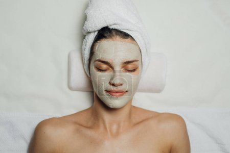 Photo pour Belle jeune femme blanche avec un masque facial naturel sur son visage couché sur la table de massage . - image libre de droit