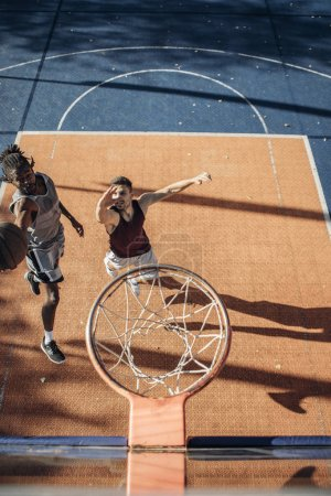 Above view of two handsome and young basketball players in a basketball duel under the hoop.