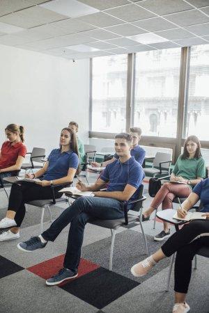 Group of high school students following teacher's presentation.