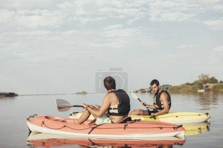 Two young Caucasian men kayaking.