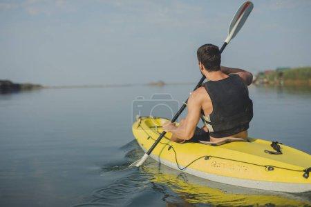 Man wearing life vest kayaking.