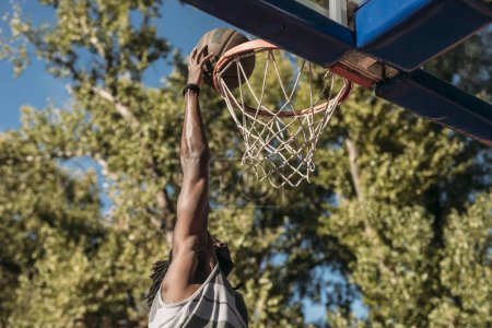 A basketball player shooting on outdoor court.