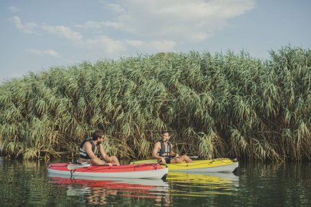 Two young Caucasian men wearing life vest kayaking near the high grass.