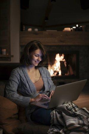 Photo pour Belle femme souriante assise près de la cheminée sur le sol en bois et tapant sur son ordinateur portable . - image libre de droit
