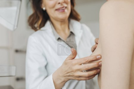 Photo pour Gynécologue femme faisant l'examen des seins à son patient. - image libre de droit