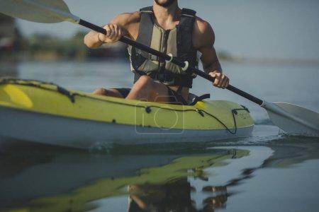 Young Caucasian man wearing life vest kayaking.