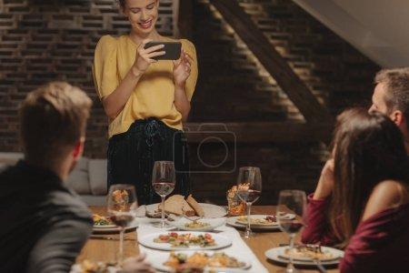 Freunde fotografieren mit Handy bei Dinnerparty zu Hause.