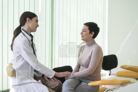 Cheerful smiling woman doctor talking with her patient at hospital.