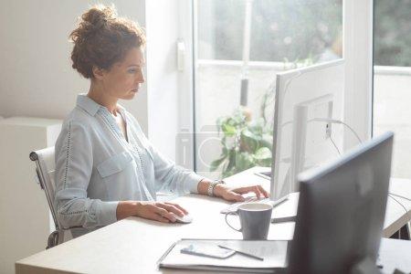 Photo pour Jeune femme travaillant sur un ordinateur de bureau à l'aide d'une souris et un clavier à l'espace de bureau moderne. - image libre de droit
