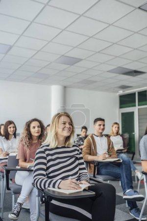 Photo pour Groupe d'étudiants prenant des notes dans une salle de classe moderne . - image libre de droit