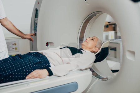 Unrecognizable medical technician pressing buttons on the CT scanner while his patient is lying on the CT scanner bed.