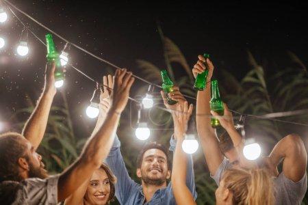 Photo pour Groupe d'hommes et de femmes de grillage avec des bouteilles de bière à la fête en plein air. - image libre de droit
