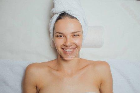 Photo pour Portrait de jeune femme souriante bénéficiant d'un traitement de beauté dans un centre de spa et regardant la caméra . - image libre de droit