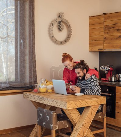 Photo for Young man and woman spending time at home and using cell phone and laptop. - Royalty Free Image