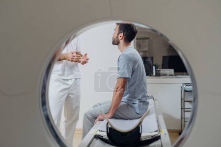 Photo pour Technicien médical méconnaissable debout et parlant à son patient assis sur le lit du scanner CT . - image libre de droit