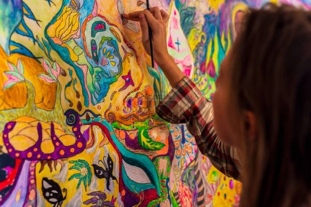 Foto de Young female artist doodling on the wall, bright psychedelic mind flow deep relaxation painting - Imagen libre de derechos
