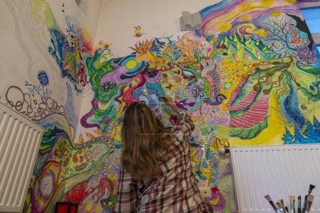 Photo pour Jeune artiste féminine gribouillant sur le mur, esprit psychédélique vif couler peinture de relaxation profonde - image libre de droit