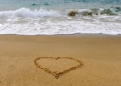Heart shape handwriting sign on the sand beach