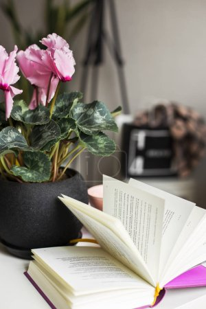 Photo for Beautiful pink f flowers in pot and book on  background - Royalty Free Image