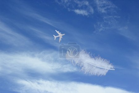 Photo for Airplane with feather in blue sky with clouds - Royalty Free Image