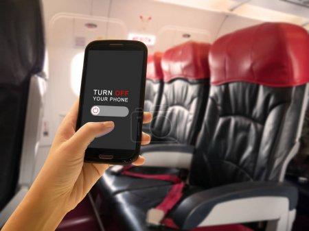Photo pour Concept de sécurité en vol. Le passager éteigne les appareils électroniques portables et le téléphone mobile ou utilise le mode de vol à bord d'un avion à bord d'avions de ligne entre le service de vol - image libre de droit