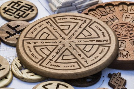 Wooden household items with ancient Slavic Nordic handmade symbols crests, runes, hats.