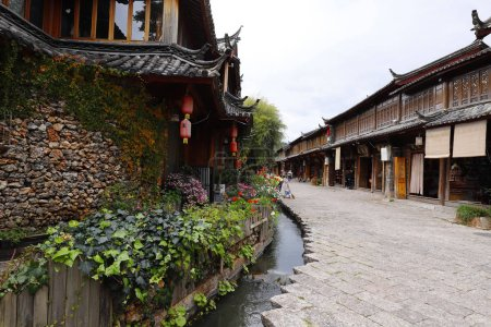 Photo for Lijiang, Yunnan, China - November, 2018. A view of a street with houses, flowers and canals of the ancient city of Lijiang, Yunnan, China - Royalty Free Image