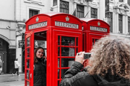 Tourists shooting with phone booth in London, England
